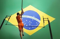 Retrovisione integrale dell'atleta maschio che salta sopra la barra contro la bandiera brasiliana Fotografia Stock