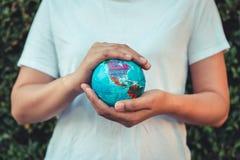 Retten Sie die Erde und Sorgfalt-Umwelt-Konzept, Nahaufnahme-Porträt der Frau hält Modell global in ihren Händen auf Baum-Urlaub lizenzfreies stockfoto
