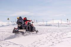 Retter auf Schneemobil fahrung in den Bergen Lizenzfreie Stockbilder