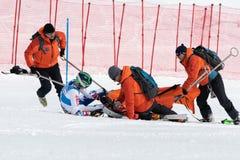 Retter stellen erste Hilfe zum Sportler zur Verf?gung, vor evakuiert auf Rettungsbahre vom Berg lizenzfreie stockfotografie