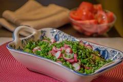 Rettiche und grüne Zwiebeln geschnitten Salat Die Porzellanplatte Lizenzfreie Stockbilder