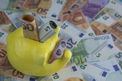 Rettung von fünfzig Euros Rechnungen in ein Sparschwein lizenzfreie stockbilder