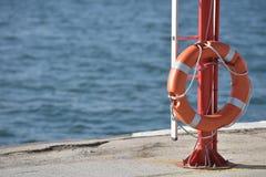 Rettungsgürtel auf der Küste mit Meer Stockbild