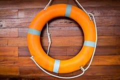 Rettungsgürtel, der auf die hölzerne Wand schwimmt Stockbilder