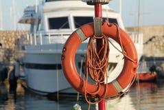 Rettungsgürtel im orange Plastik im Hafen mit einem Boot in der Rückseite Lizenzfreie Stockbilder