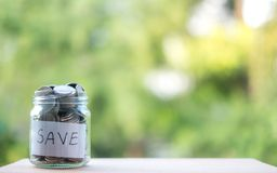 Rettungsgeld in Flasche für lösen zukünftige Investition, mit einem grünen Hintergrund ein lizenzfreie stockfotografie