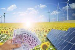 Rettungsgeld unter Verwendung der grünen Energie von den photo-voltaischen Sonnenkollektoren und von den Windkraftanlagen stockfotos