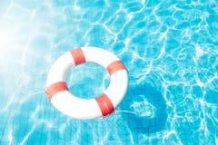 Rettungsring, der auf blauen Swimmingpool schwimmt Stockfotografie