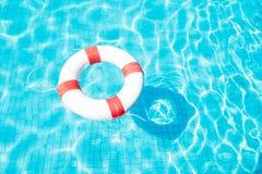 Rettungsring, der auf blauen Swimmingpool schwimmt Stockfoto