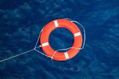 Rettungsring in einem stürmischen blauen Meer, Schutzausrüstung im Boot Lizenzfreies Stockfoto