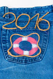 Rettungsring und Seil nummerieren 2016 auf Jeanstaschenhintergrund getont Stockfotografie