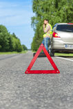 Rettungszeichen auf dem Straßenrand, Fahrer mit Telefon und defektem Auto lizenzfreie stockfotografie