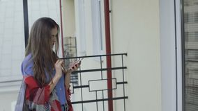 Pretty girl with make-up using smartphone on a balcony 4K. Retty girl with make-up using smartphone on a balcony 4K stock video