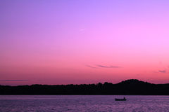 Return. A fisherman returns home in the evening with the pink Royalty Free Stock Photos