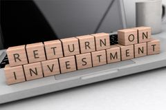 Return on Investment. Wooden letters on notebook computer - 3d render illustration Royalty Free Stock Photo