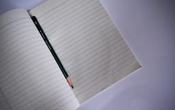 A yellowed notebook and pencil on white background stock images
