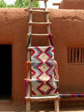 Return to the Past. Hand-woven rug on a wooden ladder in front of an adobe home in New Mexico Stock Photos