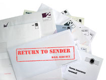 Return to Sender. A pile of unwanted mail. the top envelope showing rubber stamp stating: return to sender Royalty Free Stock Image