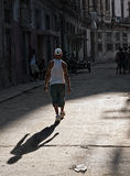 Return to the Shadows. A man walking into the shadows of a derelict area of Havana, Cuba Royalty Free Stock Photo