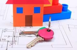 Returnera av kulört papper, tangenter och byggnadskvarter på teckning av huset Arkivbilder