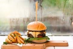 Returnera den gjorda hamburgaren med nötkött, grönsallat, ost, tomaten och potat arkivbild