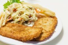 Returnera gjord fish&chip med sallad på den vita maträtten Fotografering för Bildbyråer