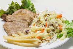 Returnera gjord köttbiff med franskt flyger på den vita maträtten Royaltyfria Bilder