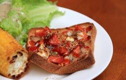 Returnera gjord pizza på fyrkanten skivat bröd med grillad havre och grönsallat i den vita runda plattan på trätabellen arkivbild