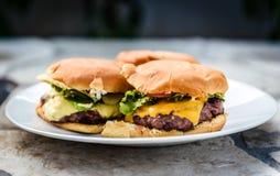 Returnera gjorda hamburgare på en platta på stenen stenlagd terrass Arkivbilder