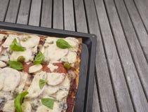 Returnera gjort tätt upp från ovannämnt på gjord organisk pizza för italienare nytt hemmet med tomater, ost, löken, oliv och göra royaltyfri foto