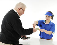 Returning Change. A teen fast-food server returning change to a senior men customer.  On a white background Royalty Free Stock Photo