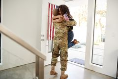 Returning millennial African American  soldier lifting his wife off her feet in the doorway of their home royalty free stock images