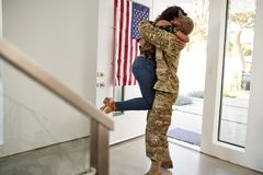 Returning millennial African American  soldier lifting his wife off her feet in their home, side view royalty free stock photo