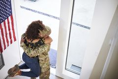 Returning millennial African American  soldier lifting his wife off her feet in the doorway of their home, elevated view. Returning millennial black soldier royalty free stock photos