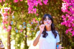 Happy beautiful young woman blowing soap bubbles outdoor. stock image