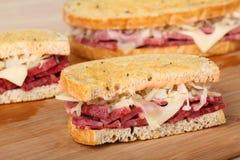Reuben Sandwich. Sliced reuben sandwich with corned beef, sauerkraut and swiss cheese Royalty Free Stock Photography