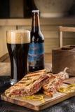 Reuben Sandwich grillé avec de la bière foncée sur la planche à découper en bois photo libre de droits