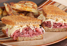 Reuben Sandwich Meal. Grilled reuben sandwich with pastrami and swiss cheese on a plate Royalty Free Stock Photos
