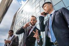Reunião da equipe do negócio e da utilização smartphones fora perto do prédio de escritórios fotografia de stock royalty free