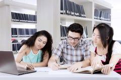 Reunião de grupo internacional dos estudantes em uma biblioteca Fotos de Stock