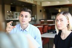 Reunião de negócios em homens bonitos novos de um café Imagem de Stock