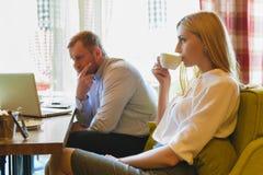 Reunião de negócios em um café A mulher bebe o café e o homem olha o portátil Foto de Stock Royalty Free