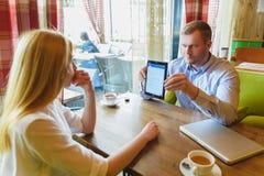 Reunião de negócios em um café O homem desapontado mostra uma tabuleta à mulher Imagens de Stock