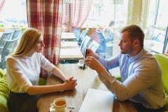 Reunião de negócios em um café O homem desapontado mostra uma tabuleta à mulher Fotos de Stock Royalty Free
