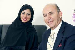 Reunião de negócios entre um homem de negócios superior & uma mulher que vestem Hijab fotografia de stock