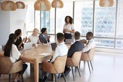 Reunião de Stands To Address da mulher de negócios em torno da tabela da placa fotografia de stock