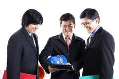 Reunião de três homens de negócios e tabuleta da utilização Imagens de Stock Royalty Free