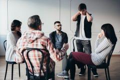 Reunião do apoio com o psiquiatra para viciados no centro de reabilitação fotografia de stock