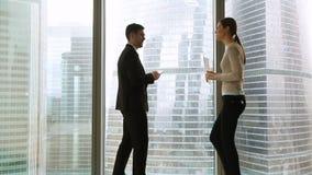 Reunião do homem de negócios e da mulher de negócios no escritório que está pela janela completo filme