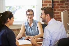 Reunião dos pares com o conselheiro financeiro no escritório Fotografia de Stock